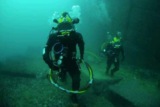 image of two underwater welders at the bottom of the river