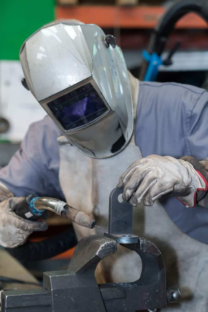 image of a welder in mask welding metal and sparks metal close