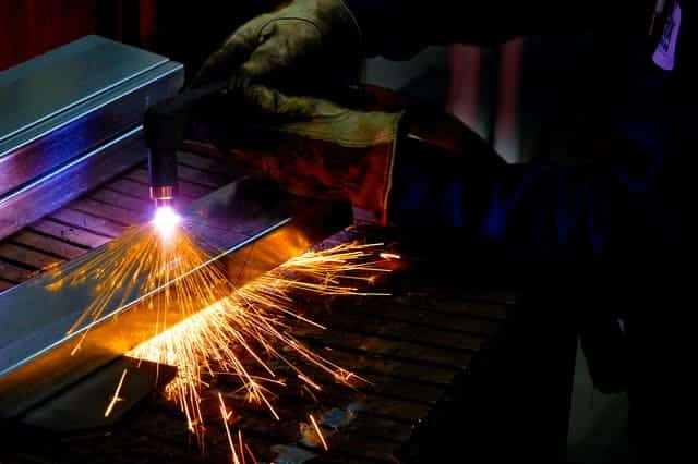 image of a worker cutting metal with plasma cutter