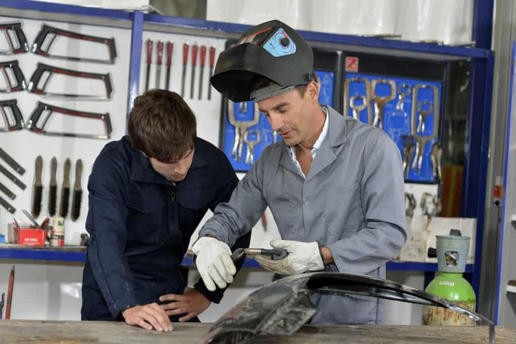Trainee with instructor using welding machine
