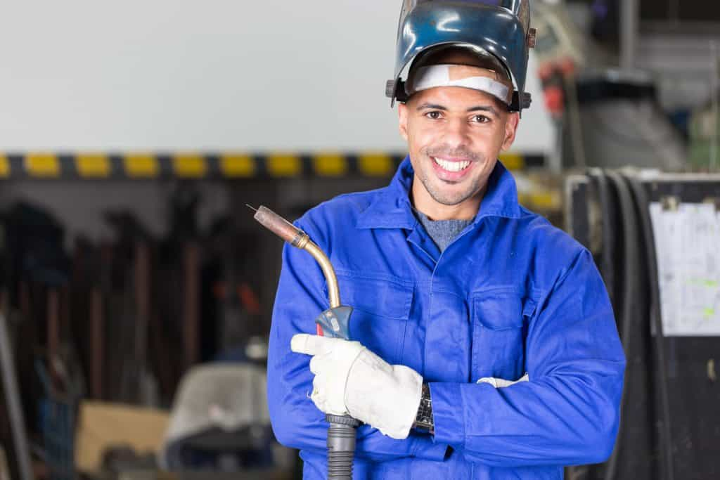 Professional welder posing with wellding machine and torch