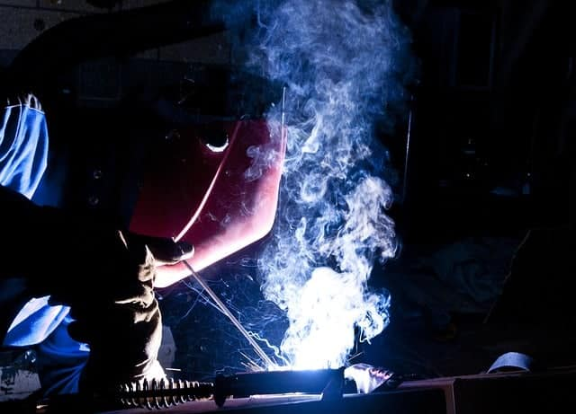 image of a worker laying a stick weld