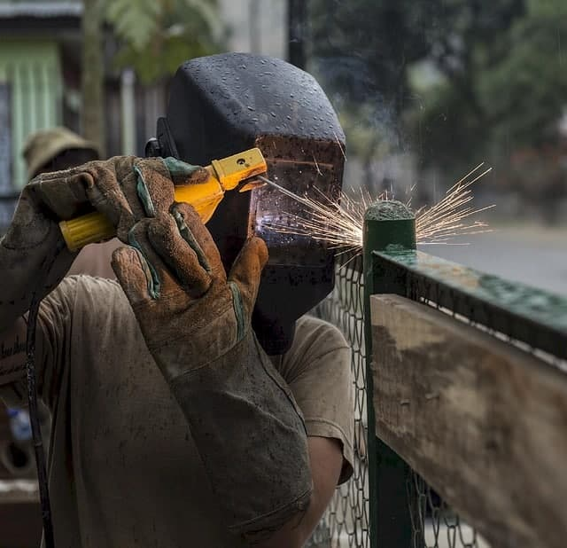 image of a welder working on a fence