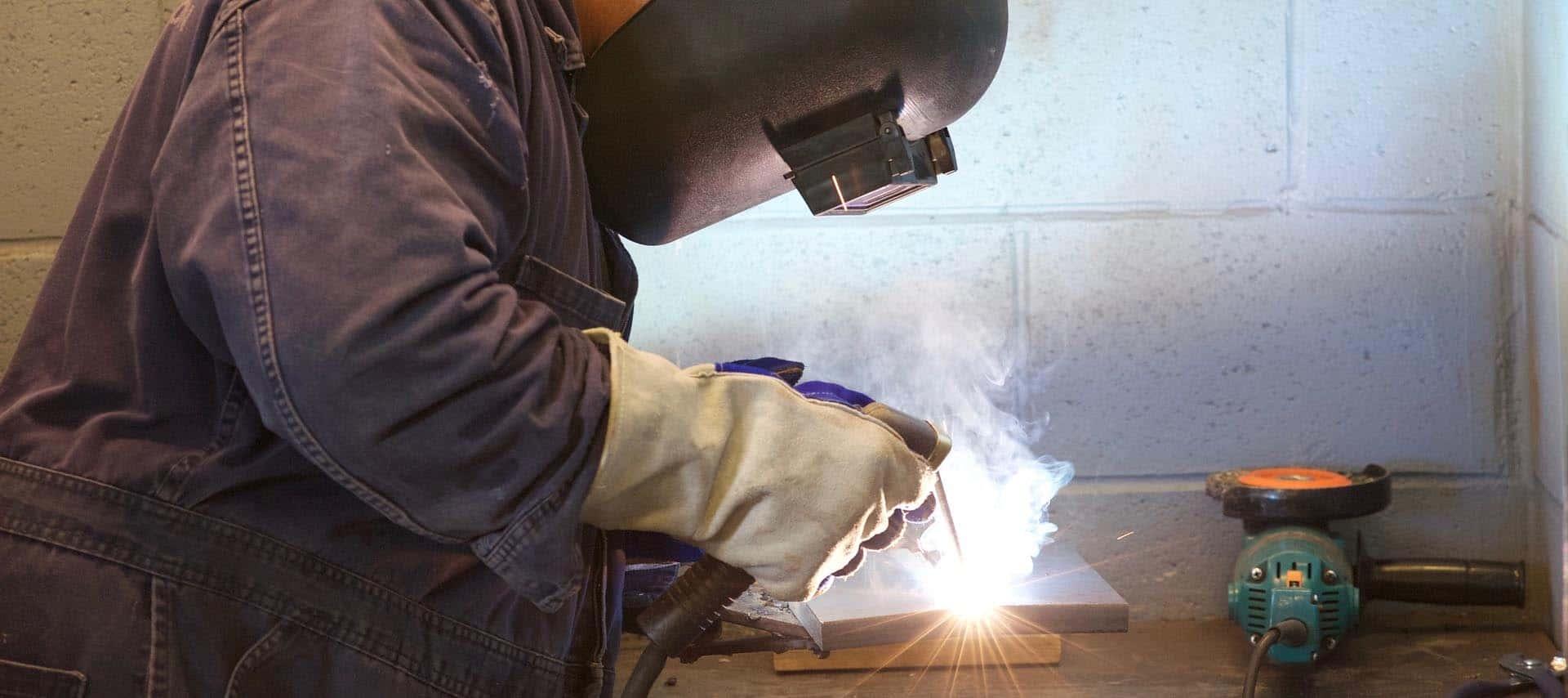 image of a worker welding in his garage
