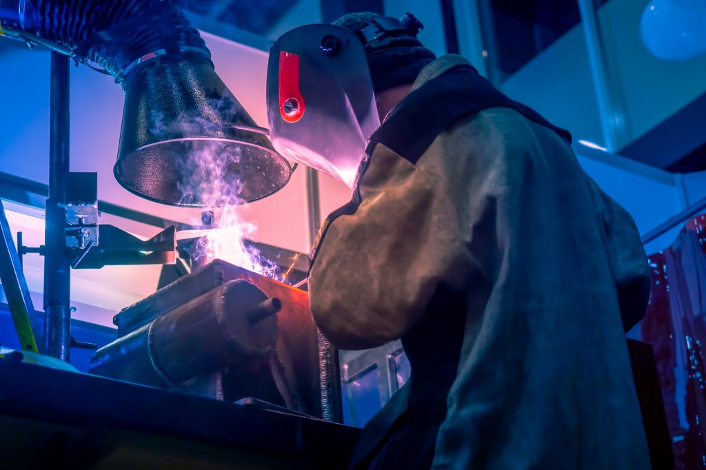 Welder welding while the fumes have been taken by the respirator safely away from the welders face