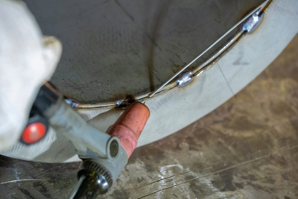 Welding of stainless steel pipe by electric arc welding in argon shielding gas. TIG welding.