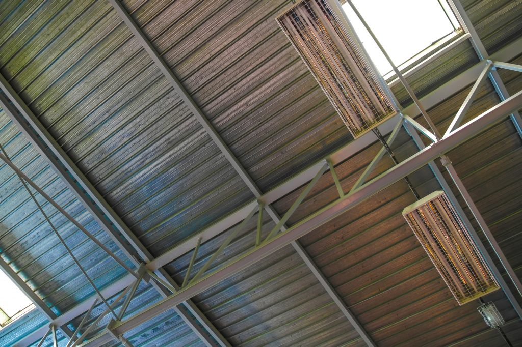 View on the ventilated ceiling of an industrial building with lamps.