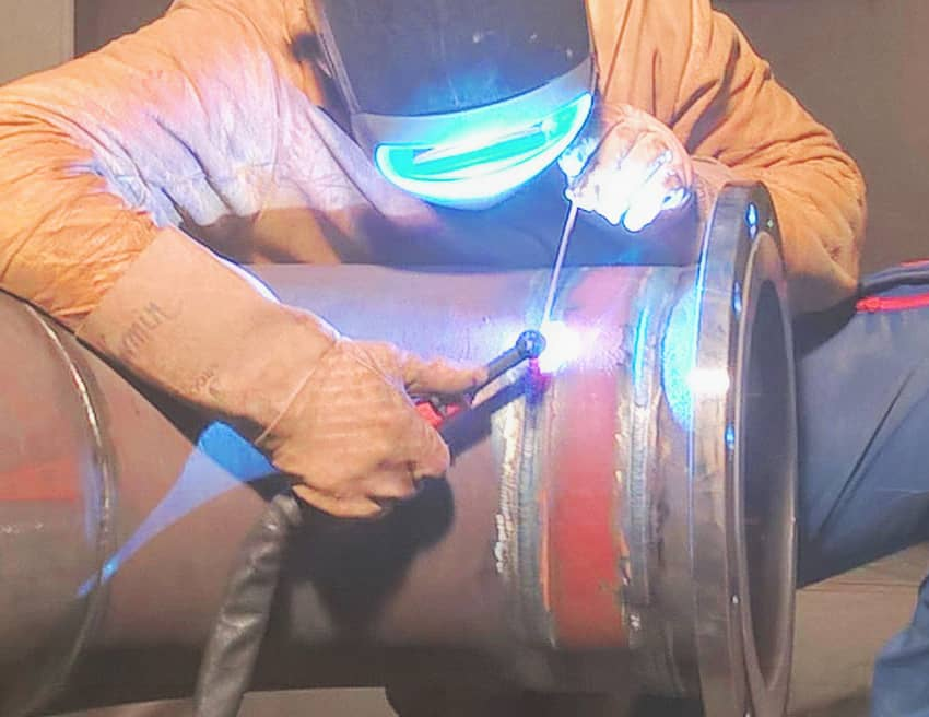 image of a worker TIG welding a pipe