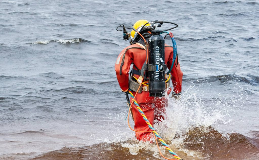 image of a commercial diver walking into the sea